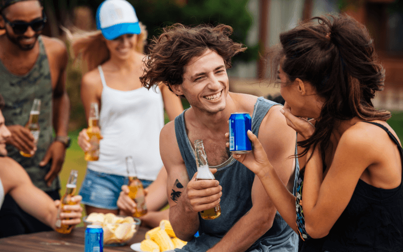 Friends having fun while drinking beer outdoors