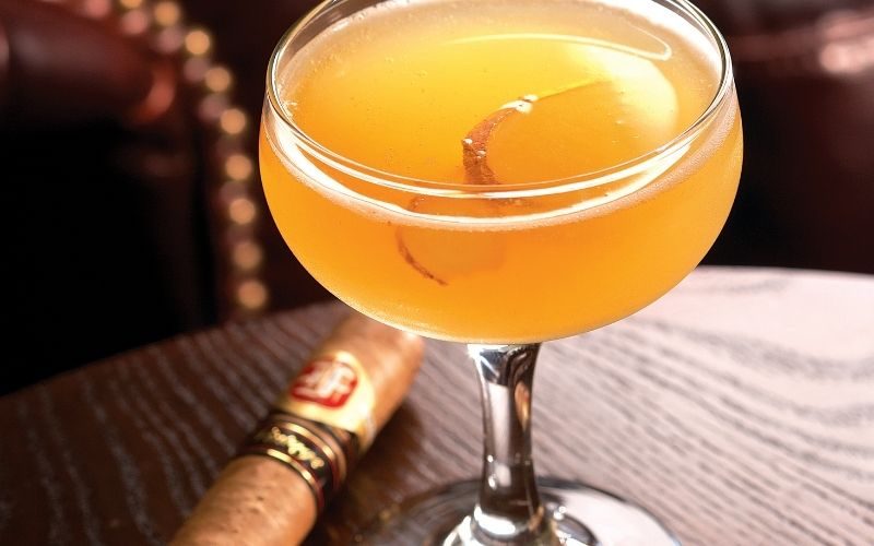 Cocktail and cigar on a wooden table