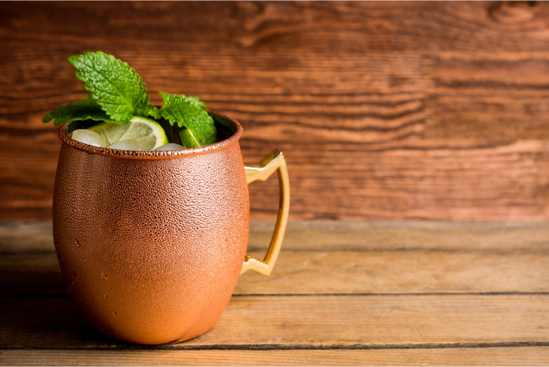 Cold Moscow Mule cocktail in copper mug on rustic background