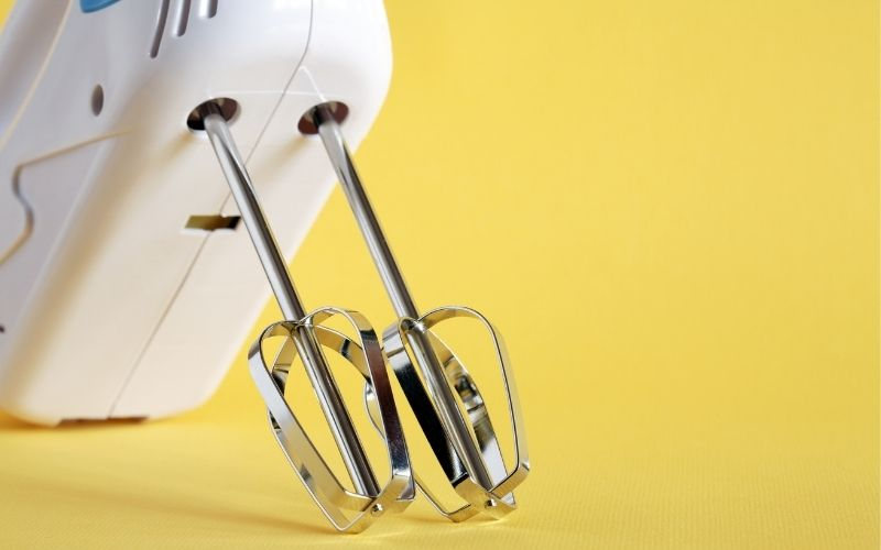 Electric mixer in yellow background