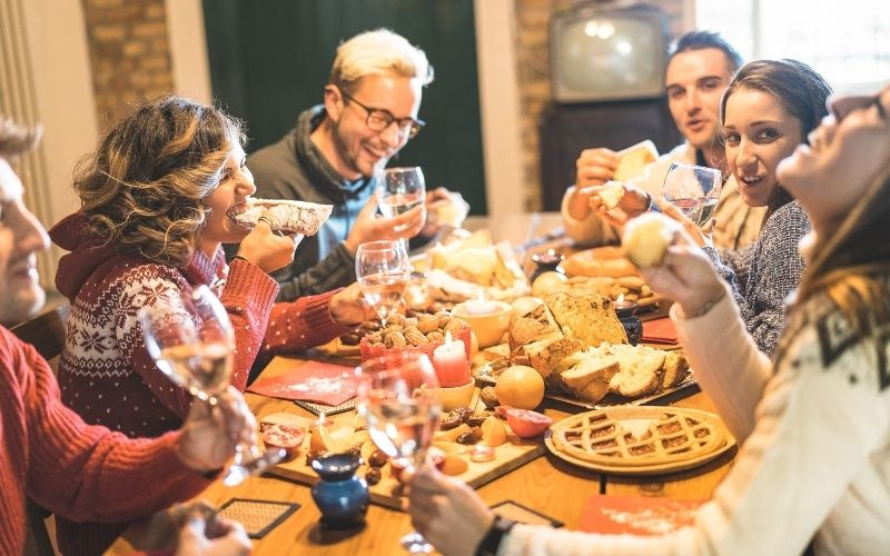 Friends talking, drinking wine, and eating at a table