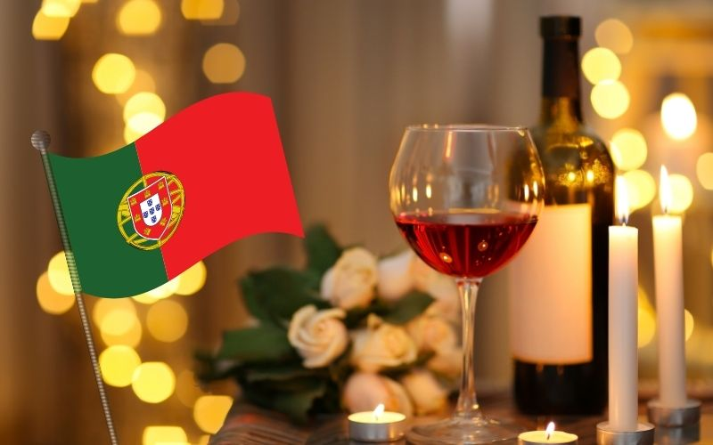 Glass and bottle of wine, candles with Portugal's flag