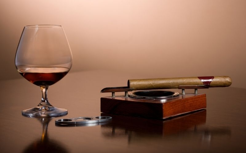 Glass of rum beside a cigar on an ashtray