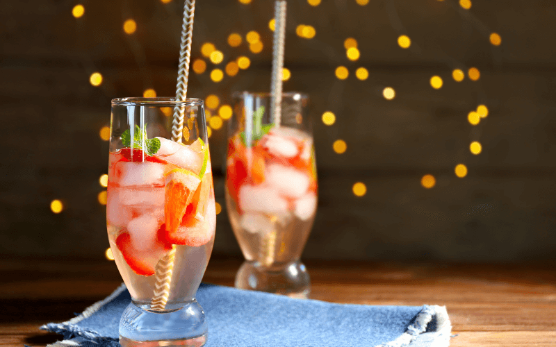 Glasses of strawberry spritzer with blurred lights background