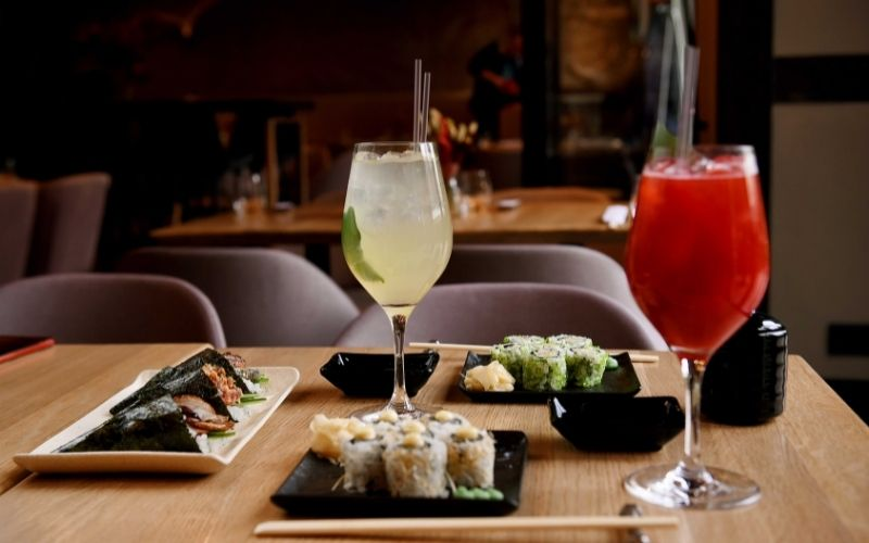 Glasses of vodka and cocktail with plates of sushi