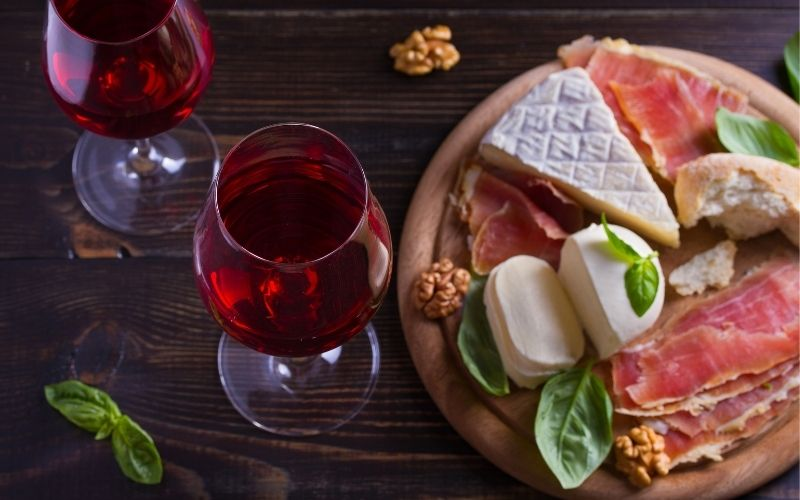 Glasses of wine with cheese, bread, nuts, and prosciutto