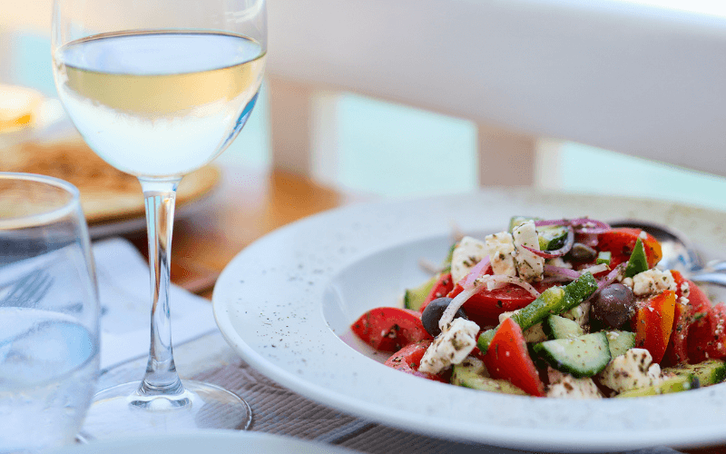 Greek salad with white wine on a table