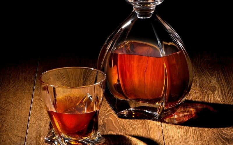 Liquor in decanter and glass on a black background
