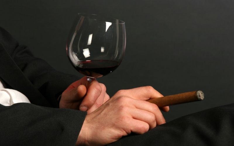 Man holding a Glass Of Wine and Cigar
