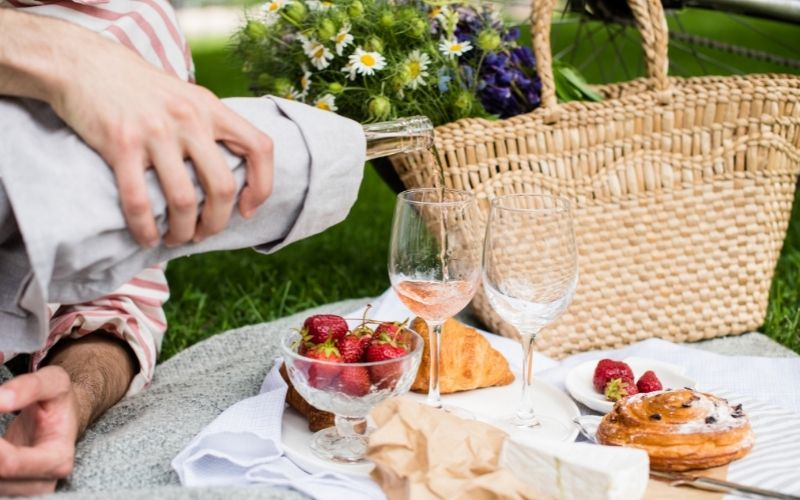 Man's Hand Pouring Rose Wine into Glasses, Summer Picnic