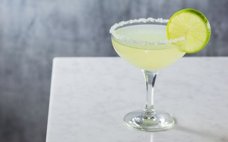 Margarita garnished with a salt rim and a lime wheel