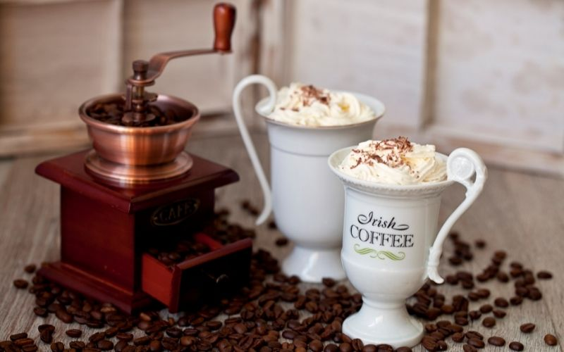 Coffee in a coffee grinder and Irish Coffee drink in a white mug