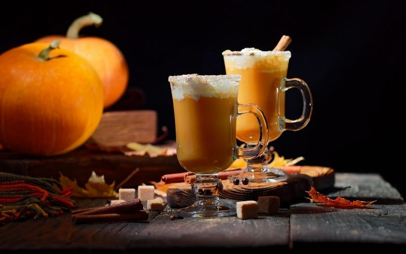 2 glasses of Not Your Basic PSL with pumpkin on the background