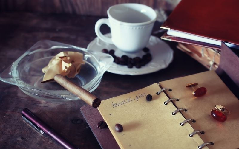 Notebook with cigar and cup of tea