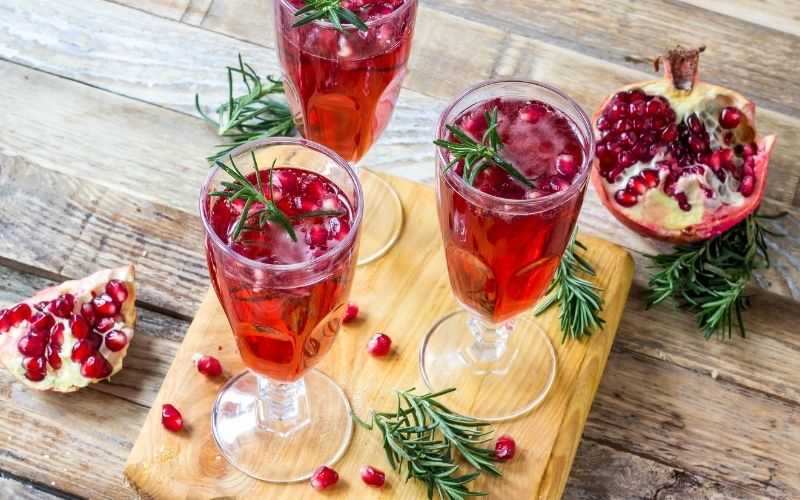 Pomegranate Fizz on cutting board with rosemary
