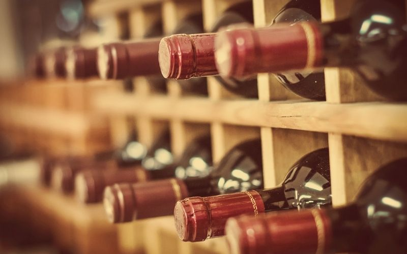 Red wine bottles stacked in a wine rack
