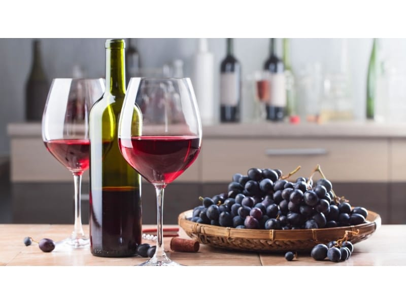 Red wine glasses with a wine bottle and grapes on top of the table