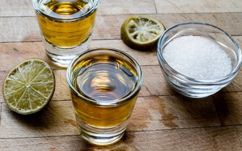 Shots of tequila and mezcal with dried lime and sugar