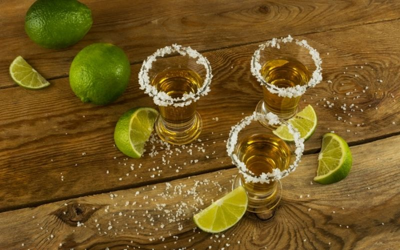 Tequila shots with lime in the background