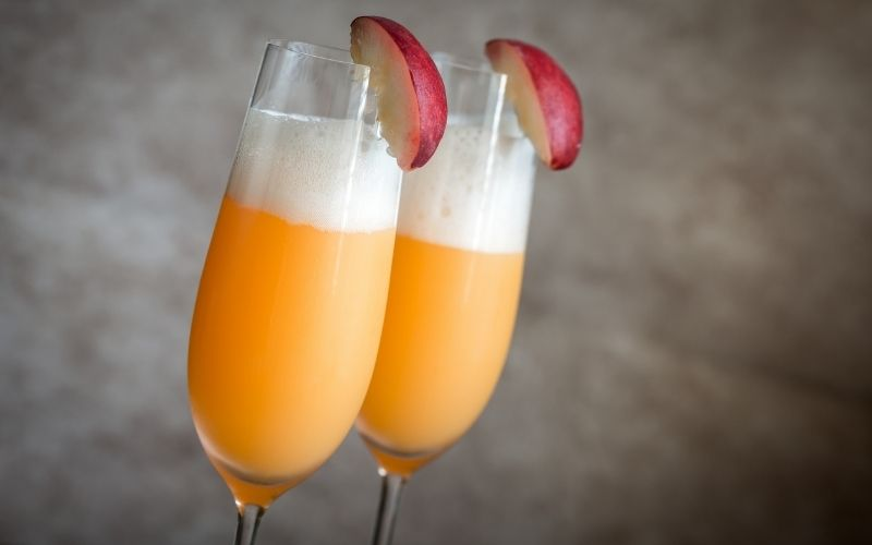 Two Bellini cocktails with peach slices