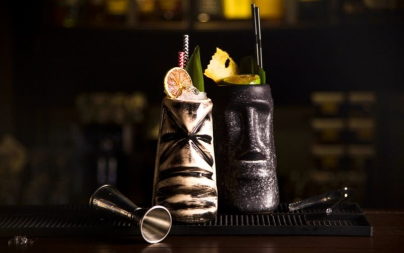 Two glasses of Zombie cocktail garnished with lime wedges and cocktail umbrellas