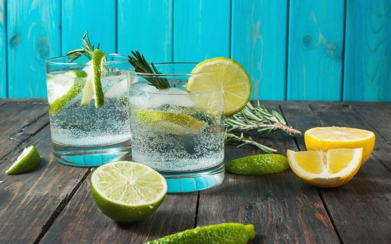 Two glasses of gin and tonic with limes, lemons, rosemary as garnish