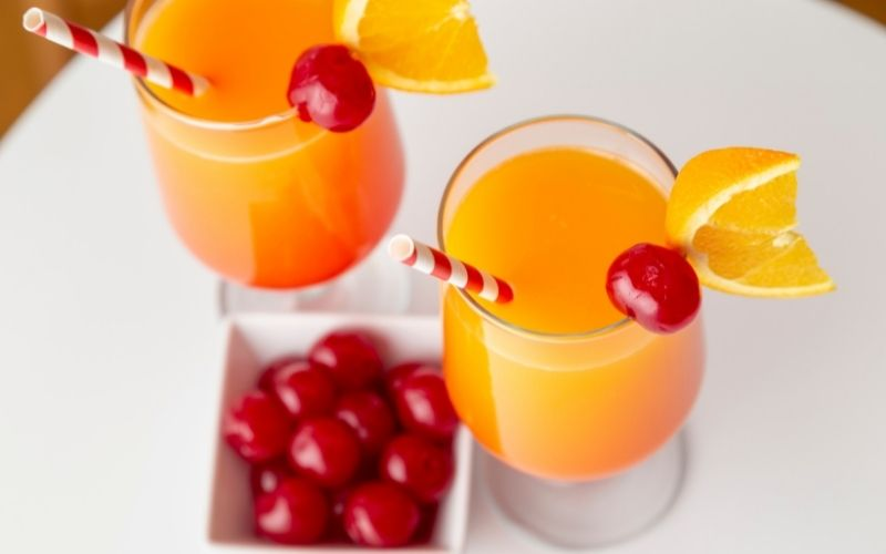 Two glasses of tequila sunrise garnished with cherries