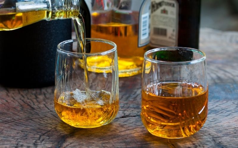 Two glasses with whiskey pouring in over a wooden table
