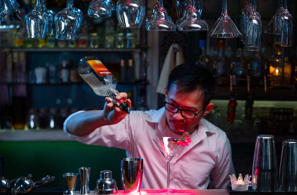 Professional barman pouring blue liquor from bottle into cocktail shake