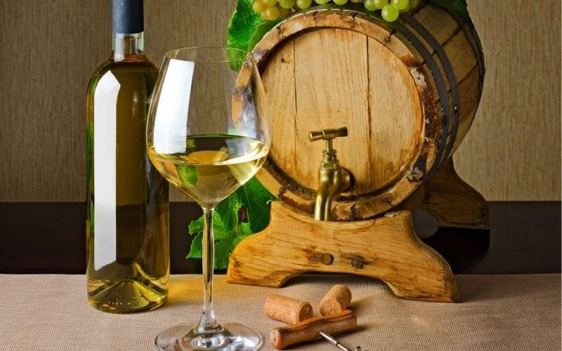 White Wine in glass and bottle with a Barrel