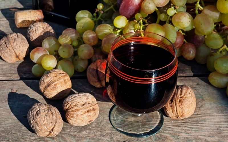 Wine on the Table with Grapes and Walnut