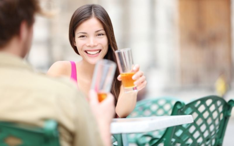Woman smiling with a glass of alcoholic drink in hand