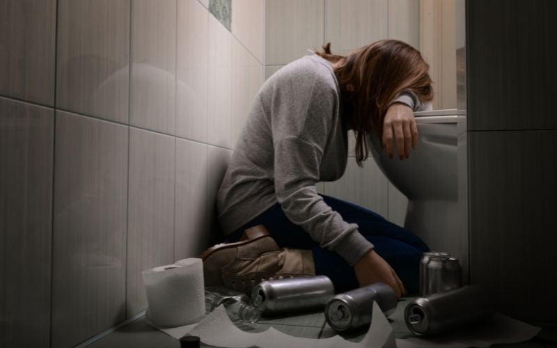 Woman unconscious in a toilet with litters of alcohol near her