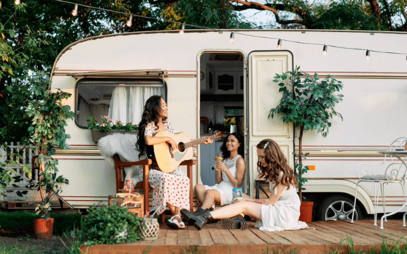 Young Happy Women Have Fun Together Enjoy Picnic near RV