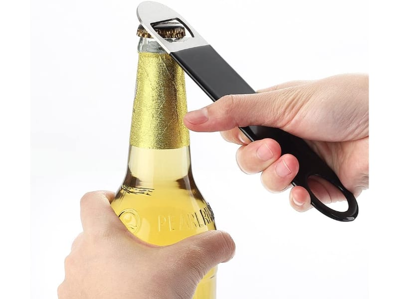 A bar key being used to open a bottle of beer