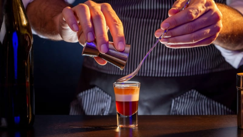 A bartender adding some liquid using the bar spoon and jigger