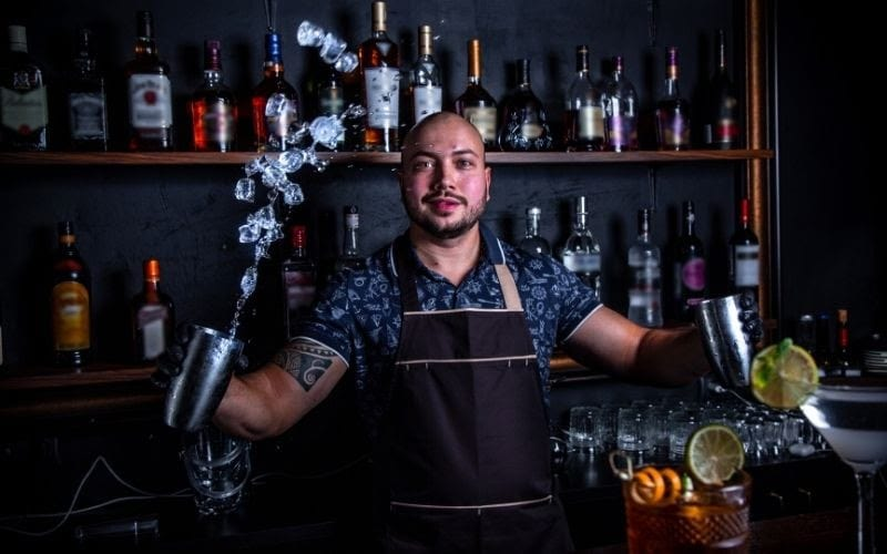 A bartender doing ice throwing