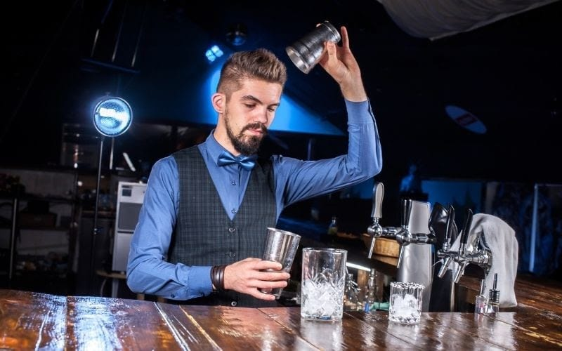 A bartender holding a cocktail shakers