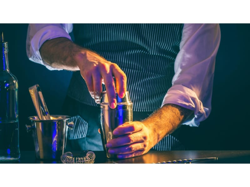 A bartender opening a cocktail shaker