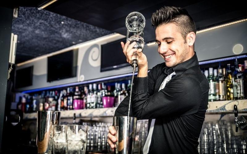 A bartender pouring liquor into the cocktail shaker