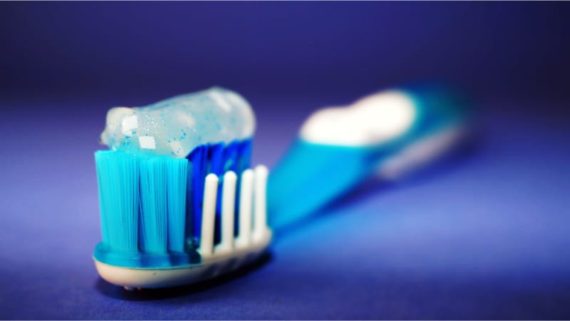 A blue toothbrush with toothpaste on it