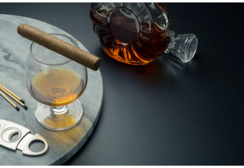 a Cuban cigar on a snifter glass of brandy