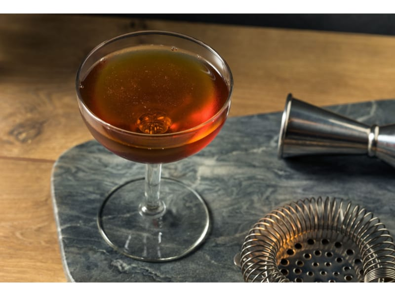 A glass of  rye with cocktail strainer and jigger