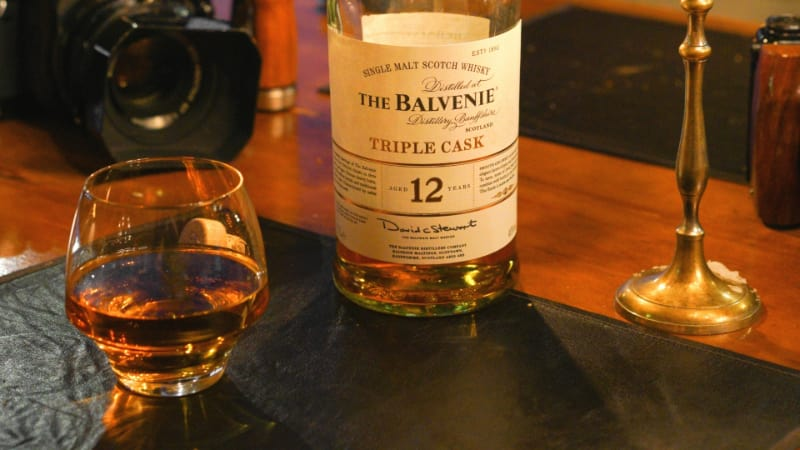 A glass of Balvenie Scotch Whiskey with a Bottle on the Background