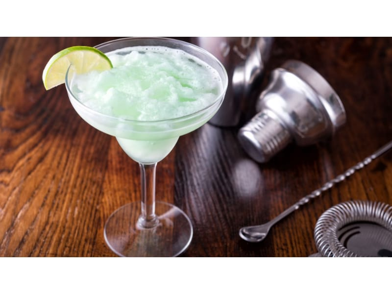 A glass of Basil Lime Daiquiri with a cocktail shaker and a stirring spoon