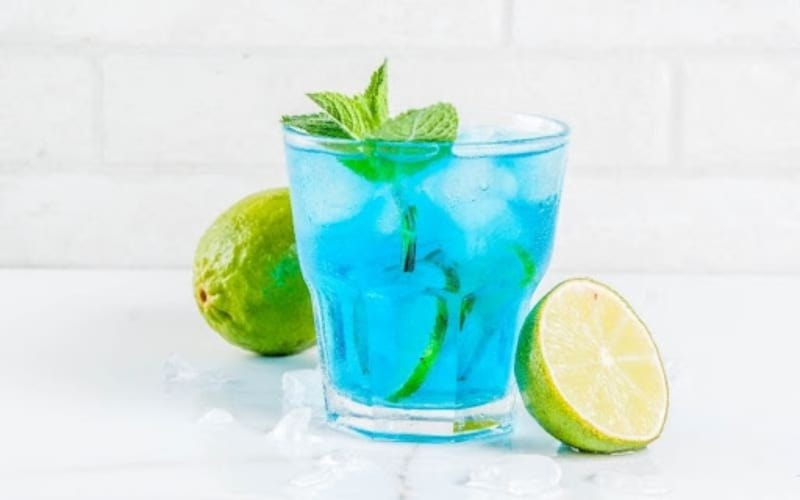 a glass of Blue Bayou cocktail with slices of lime
