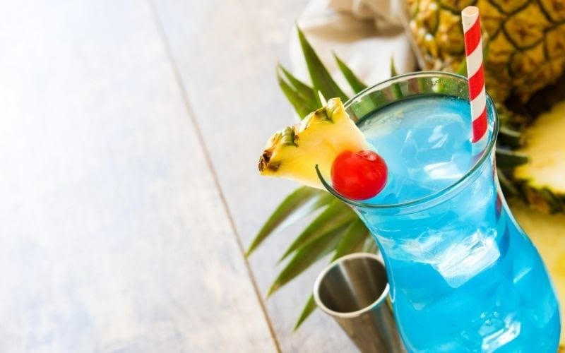 A glass of blue Hawaiian with a pineapple wedge