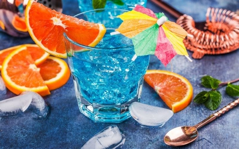 a glass of Blue Lagoon with orange wedges