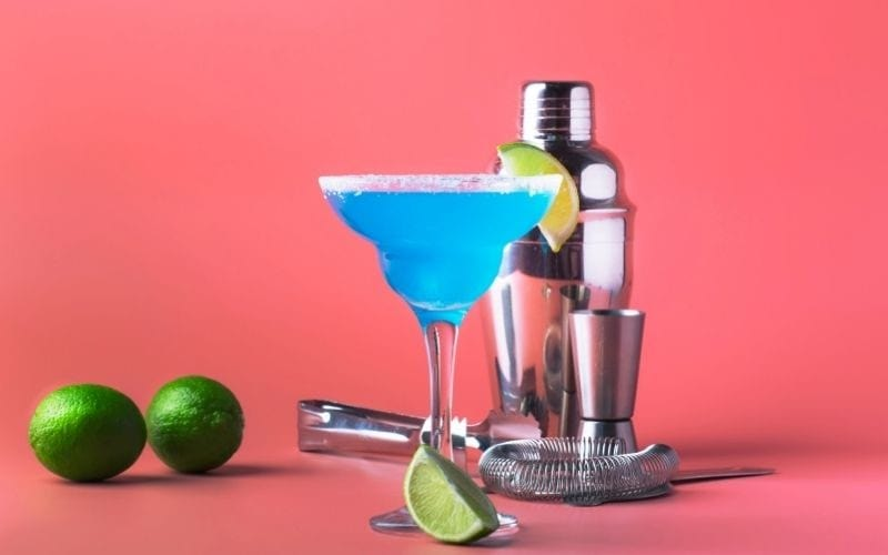 A glass of blue margarita with lime wedges and bartending tools