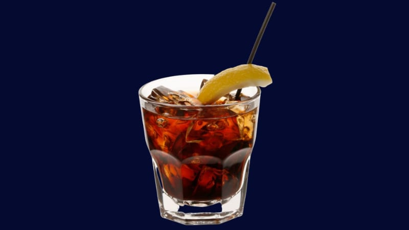 A glass of brave bull with lemon wedge and straw